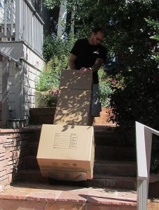 Crew member loading boxes down stairs